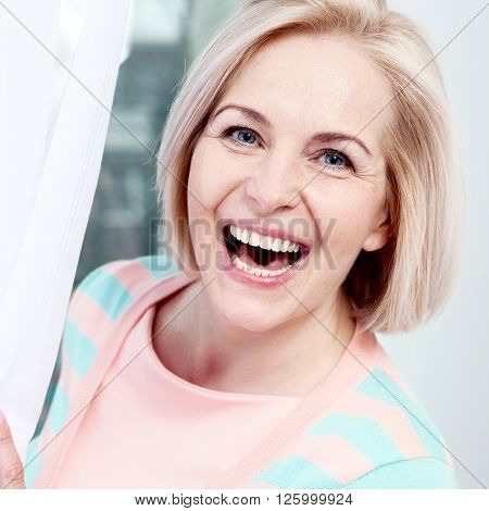 Portrait beautiful middle aged woman smiling friendly and looking into camera. Woman's face close up