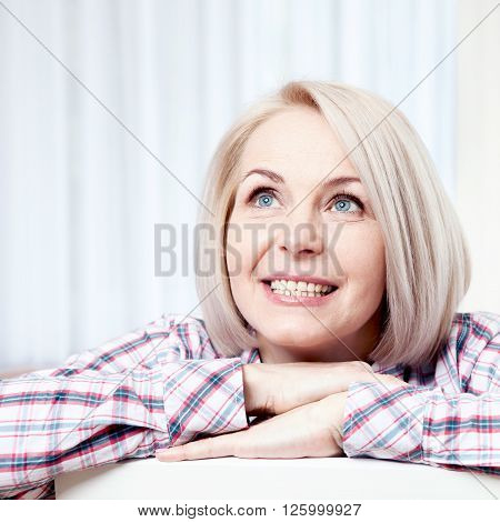 Active beautiful middle-aged woman smiling friendly and looking up at home in living room. Woman's face close up