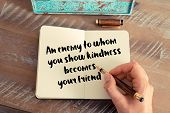 Retro effect and toned image of a woman hand writing on a notebook. Handwritten quote An enemy to whom you show kindness becomes your friend as inspirational concept image poster