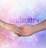Forever my Soulmate -  Man gently holding female hand with the word SOULMATES above on a sparkling glitter blue and pink bokeh background ideal for engagements, marriage proposals and wedding literature poster