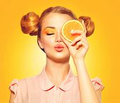 Beauty Model Girl takes Juicy Oranges. Beautiful Joyful teen girl with freckles, funny red hairstyle and yellow makeup. Professional make up. Orange Slice  poster
