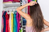 Home closet indecision woman choosing her fashion outfit on clothing rack. Shopping spring cleaning concept. Morning woman having too many clothes thinking of what to wear in organized clean walk-in. poster