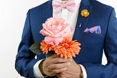 Man in blue suit with pink bow tie flower brooch and pink blue strip pocket square close up carry flowers poster