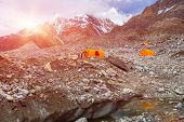 Mountain Expedition Camp on Glacier Moraine with Large Ice Crevasse and Melting Lake Foreground Clothing Hanged on Tent for Drying after Rain Sun Shining poster