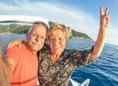 Adventurous senior couple taking selfie at Giglio Island on luxury speedboat - Active elderly travel lifestyle concept on happy tour moment - Retired people around world - Warm afternoon color tones poster