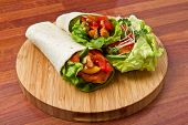 Spicy chicken with salad and salsa wrapped in a soft flour tortilla. poster