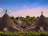 Alberobello: skyline of monumental Trulli village. ITALY,APULIA.Alberobello is a UNESCO World Heritage. Conical rooftop of trulli:It is a false dome built  with dry overlapping stones, whitewashed base and cone-shaped roof with pinnacles of various shapes poster