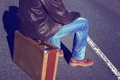 Emigration, resettlement, refugee, migration.The man in jeans with a suitcase.Photo toned in retro style. poster