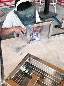 A worker welding construction by argon welding poster