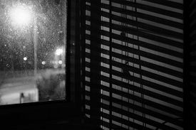 High-contrast, black-and-white image of Venetian blind shadows on a wall at night, with a corner of a grimy window (with a defocused view of the road and street lights outside) just off-centre.