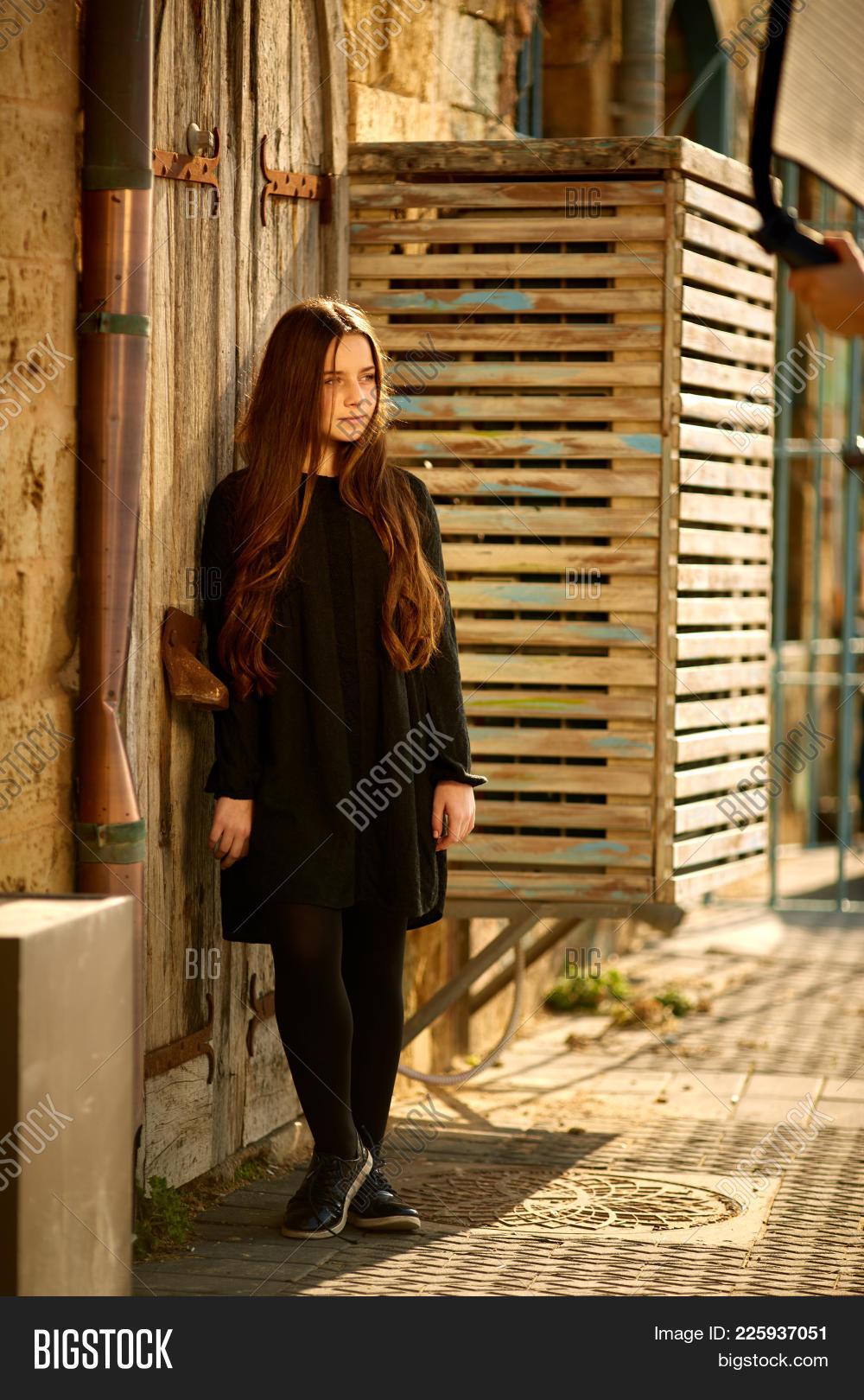 6dee6e7302e Young Beautiful Stylish Girl Walking And Posing In Short Black Dress In  City Near Fountains.