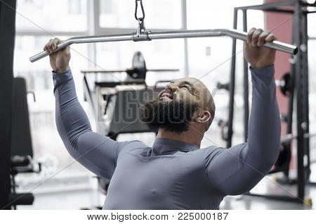 Male athlete pulling down heavy weight with strained face, sports training