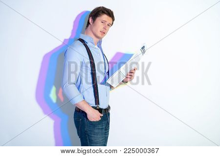 Portrait of assured male holding article while watching at camera. Multicolored shadow. Information concept
