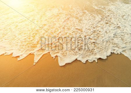 Sand beach and water wave background. Soft wave of the turquoise sea on the sandy beach.Natural summer beach in sunset background with copy space.