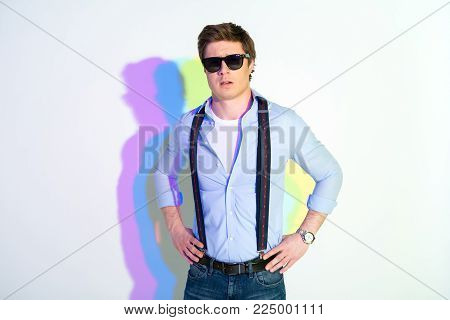Portrait of assertive male in sunglasses with hands on hips. He has multicolored shadow. Assuredness concept