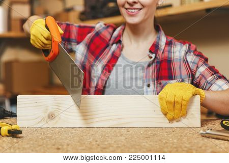 Close up smiling caucasian young brown-hair woman in plaid shirt, gray T-shirt, yellow gloves sawing piece of wood with saw, working in carpentry workshop at wooden table place with different tools