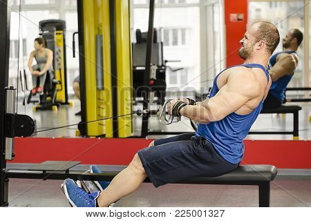 Young male doing cable row exercises with strained face, guy building muscles