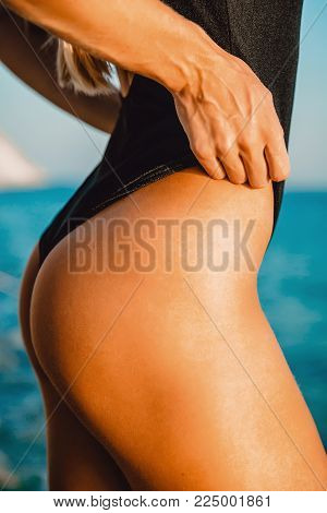 Back of beautiful woman in similar bikini on sea background.