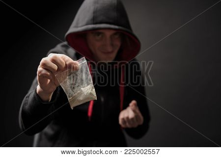 Portrait of sly drug dealer holding small bag with cocaine and looking at camera with cunning smile. Focus on package. Isolated on background