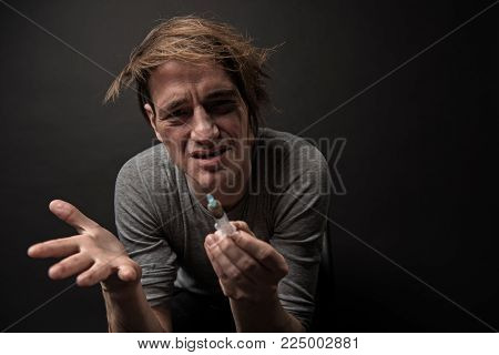 Portrait of worried hophead with disheveled hair sitting and holding hype in his hand. Copy space in left side. Isolated on background