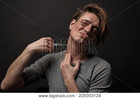 Portrait of unwell habit male using syringe on his neck and wincing in pain. Isolated on background