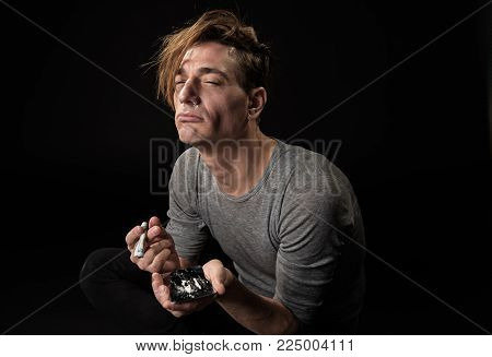 Desirous tranquil man sniffing cocaine through money tube. Isolated on background