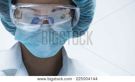Mixed-race chemist working in security goggles, conducting experiment, close-up, stock footage