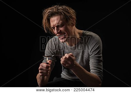 Freak in agony heating up soporific. He is holding syringe in his mouth. Isolated on background