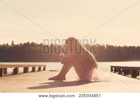Sad Beautiful teen girl is sitting with serious face at seaside during sunset.