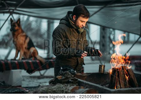 Stalker warms his hands on fire, dog on background