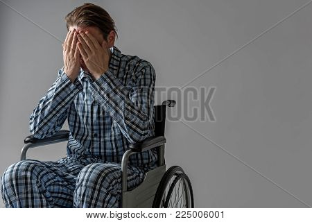Decadent male person sitting in wheelchair and covering his face with hands. He is crying. Copy space in right side. Isolated on background