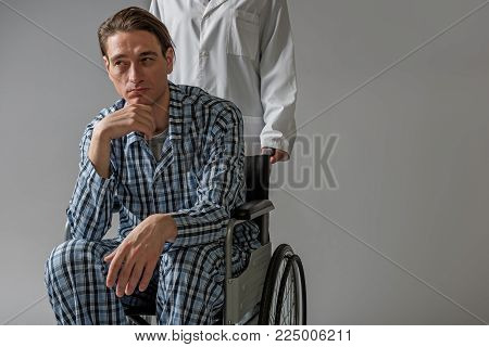 Portrait of young paralyzed man with pensive expression carrying in wheelchair by medical worker. Copy space in right side. Isolated on background