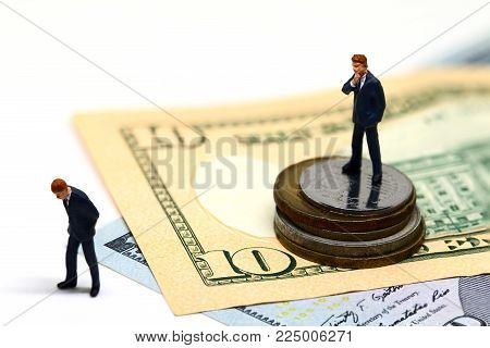Winning and losing businessmen figurines. Miniature model. Cash banknotes and coins. Successful business strategy. Withdrawal competitor from market. Profit growth. Career achievement. Fired from work