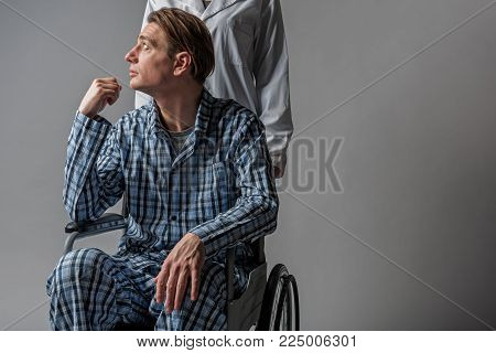 Help concept. Carer moving armchair with disabled peaceful man sitting in it. Copy space in right side. Isolated on background