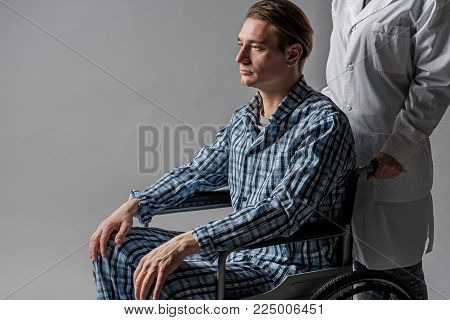 Depressed disabled taking seat in armchair. He is nursed by invalid tender. Isolated on background