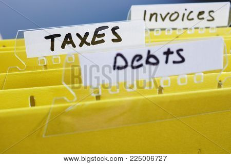 Yellow folders with title taxes and others. Accounting concept.