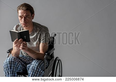 Portrait of frustrated invalid sitting in wheelchair and holding holy book. Copy space in right side. Isolated on background