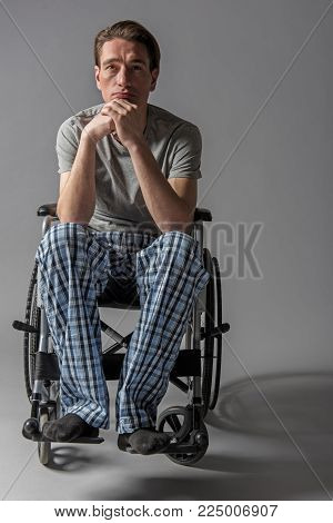 Portrait of young melancholy handicapped sitting in armchair and immersing in thoughts