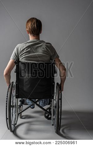 Back of guy with physical inability sitting in wheelchair. He is holding his hands on wheels