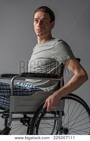 Portrait of upset man having physical condition that limiting his movements. Isolated on background
