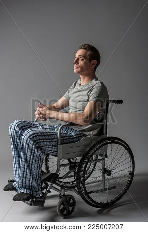 Disease concept. Side view of thoughtful invalid taking seat in special armchair