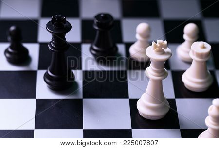 Black and white kings on chess board. Chess figure king. Black and white chess figurine. Stalemate position on chessboard. Strategic task. Business competition and risk concept. Chess game piece