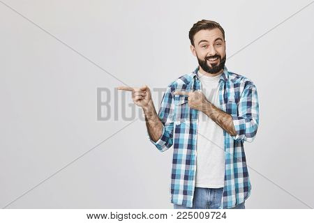 Handsome adult spouse with beard and moustache, smiling and expressing cheer while pointing left with two hands, standing against gray background. Artist offers to show his new work to close friends.