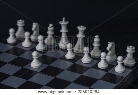 White chess figures on board. White chess set in order for game start. First move E2-E4 on checkered board. Chess figurine order. Checkmate game banner template. Intellectual sport. Tactic game