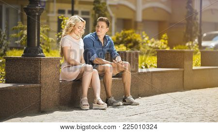 Male and female sitting on bench next to each other, feeling awkward, first date, stock video
