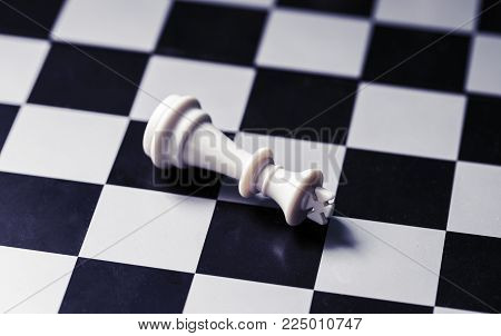 White king on chess board. King lost on checkered board. White king lies on chessboard. Mate situation in chess rules. Business advantage or strong leadership concept. Chess king closeup