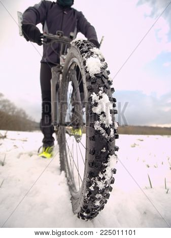 Extreme low ankle close view to mountain bicycle blocked in snowy icy trail.  Extreme wide view