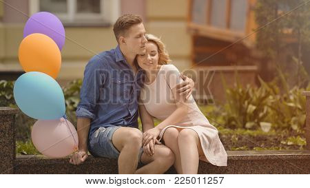 Guy with air balloons hugging his girlfriend, couple cuddling on romantic date, stock video