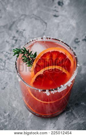 Blood Orange Elderflower Gin Cocktail with ice and thyme on dark backgorund