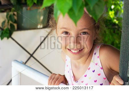 Portrait of beautiful girl smiling at the garden. Happy child